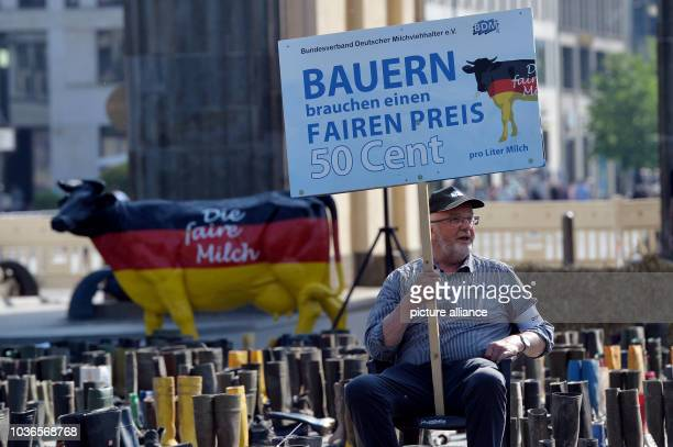 An activist with the Federal Association of German DairyCattle Owners sits with a sign written with 'Farmers need a fair price' amongst rubber boots...