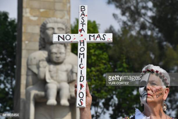 An activist woman with painted face holds a cross during a march of protest against the government in demand of the clarification of the disappeared...