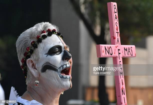 An activist woman with painted face holds a cross while shouting slogans during a march of protest against the government in demand of the...