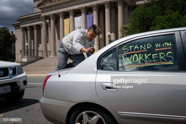 An activist writes messages on her vehicle as she participates in a May Day protest during the coronavirus pandemic, May 1, 2020 Washington, DC. May...