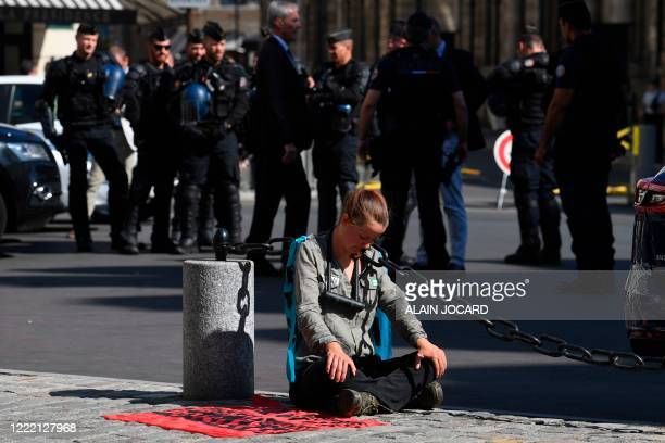 An activists from international climate action group Extinction Rebellion who locked herself to a chain outside the Ministry of Interior reacts past...