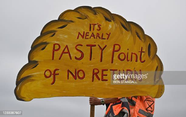 An activists from the climate change protest group Extinction Rebellion, hold a placard in the shape of a giant Cornish Pasty, during a demonstration...