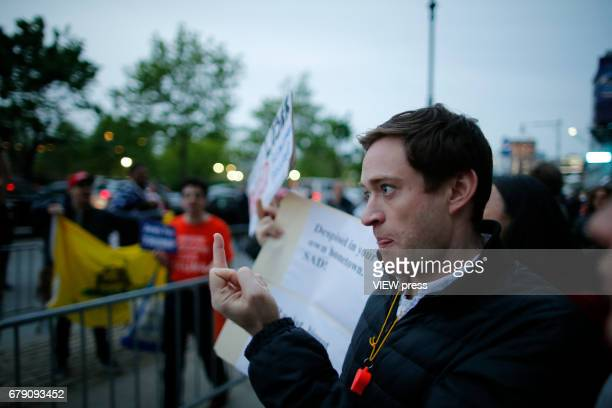 An activists gives his middle finger to supporters of US president Donald Trump as they argues near the USS Intrepid where US president Trump is...