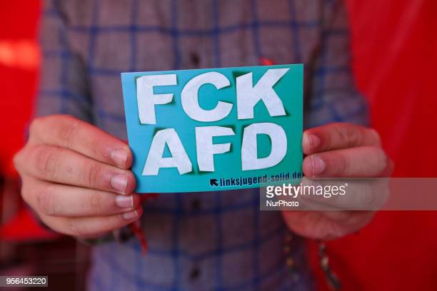 An activists holds a 'FCK AFD' sticker is seen on the Leopoldcorso in Munich Germany on May 9 2018