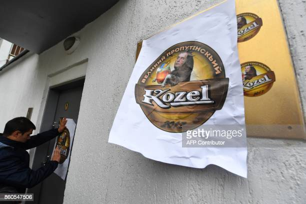 An activists of the Ukrainian farright National Corpus Ukrainian party pastes a poster at the entrance of the Czech Embassy with an image of the logo...