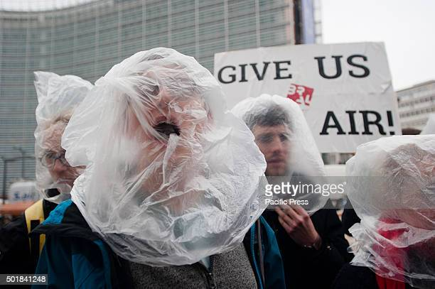 An activists pretends to be choking at the protest for clean air in front of the European council in Brussels