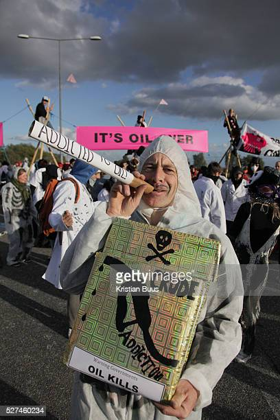 An activists spelling out the message by play smoking a gigantic cigaret Crude Oil Awakening is a coalition of climate change activist groups On...