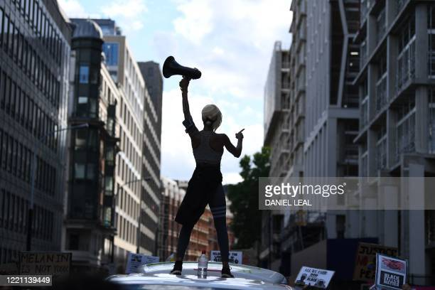 An activists with a megaphone stands on top of a van at the head of a march during a Black Lives Matter protest against racism in central London on...