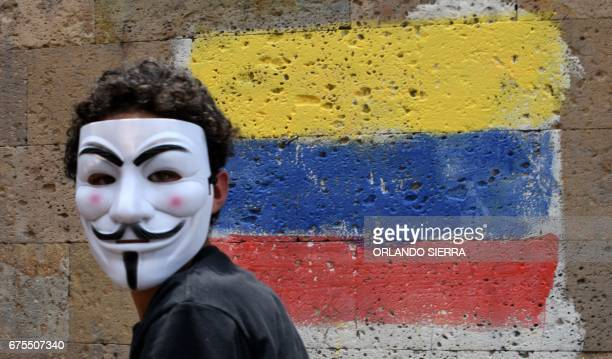 TOPSHOT An activisy wearing a Guy Fawkes mask takes part in a march during May Day celebrations in Tegucigalpa on May 1 2017 / AFP PHOTO / ORLANDO...