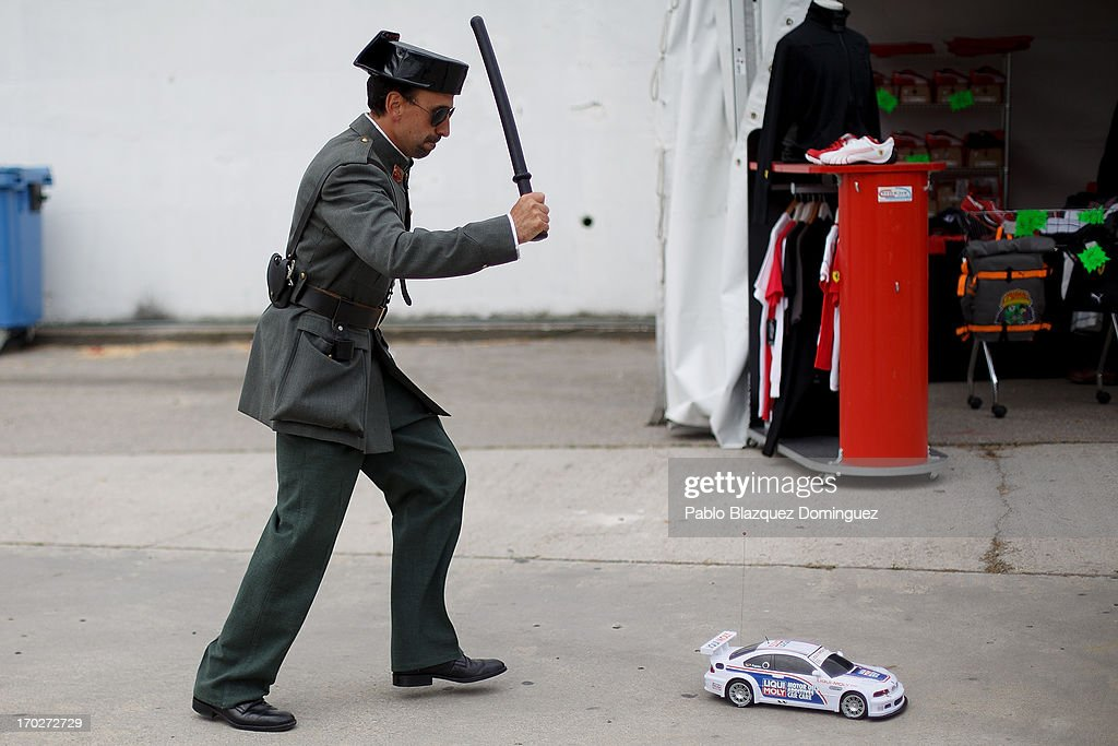 An actor dressed as a Civil Guard pretend to batton hit a toy car at the Jarama Circuit on June 9, 2013 in Madrid, Spain. The Jarama Vintage Festival seeks to revive the 1960s, 70s and 80s attracting classic cars and motorbikes against a background of public orientated activities and shows.