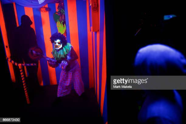 An actor dressed as a clown scares a visitor at Terror Behind the Walls haunted house on October 24 2017 in Philadelphia Pennsylvania The haunted...