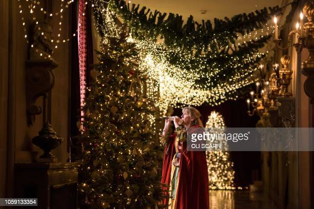 An actor dressed as a fairytale storyteller plays a horn in Chatsworth House which has been decorated for their Christmas season in various fairy...