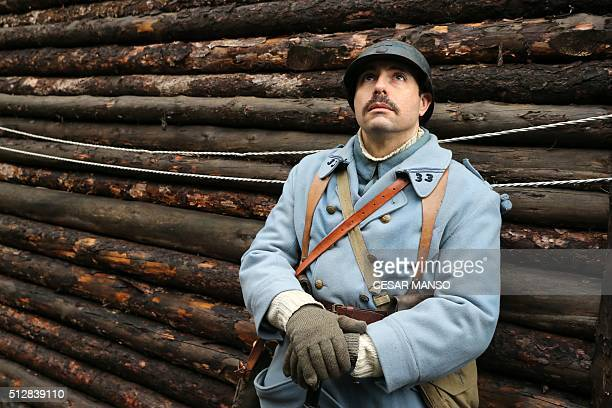 An actor dressed as a French soldier of the World War I looks up as he performs the start of the Verdun's battle in a trench of the Museum of...