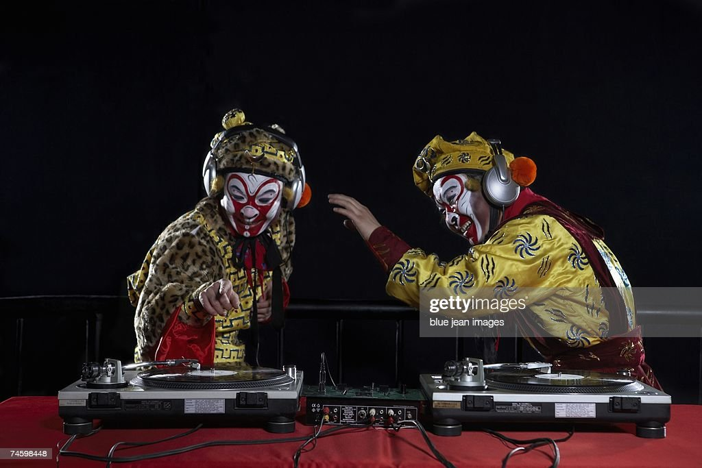 An actor dressed as a traditional Beijing Opera Monkey King and an actor dressed as a Comedian fool around and use a pair of DJ turntables. : Stock Photo