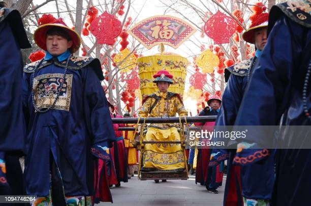 An actor dressed as an emperor is carried in a sedan chair during a reenactment of a Qing Dynasty sacrifice ceremony at the Temple of the Earth in...