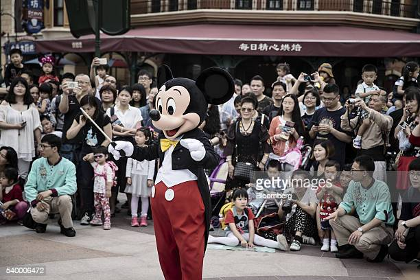 An actor dressed as Mickey Mouse raises a baton as a marching band and audience members look on at Walt Disney Co's Shanghai Disneyland theme park...