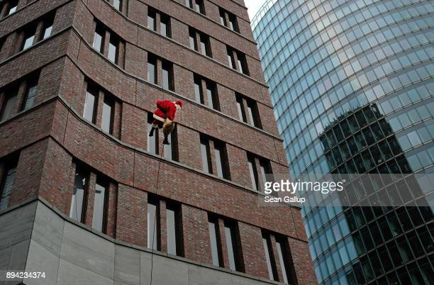 An actor dressed as Santa Claus abseils down the facade of Kollhoff Tower on December 17 2017 in Berlin Germany The premise of the short theatrical...