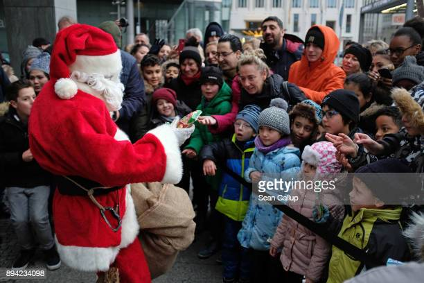 An actor dressed as Santa Claus distributes candy to children after he abseiled down the facade of Kollhoff Tower on December 17 2017 in Berlin...