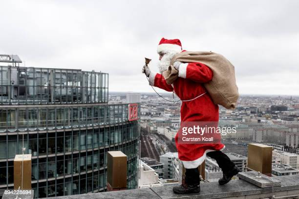 An actor dressed as Santa Claus pretends to retrieve a lost package near the top of the Kollhoff Tower on December 17 2017 in Berlin Germany The...