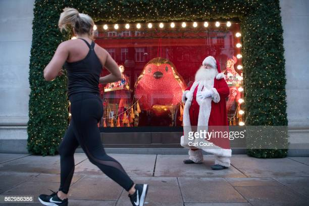 An actor dressed as Santa poses for photographs next to a Christmas window display at Selfridges on October 19, 2017 in London, England. Selfridges...