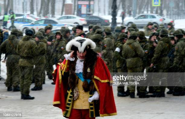 An actor dressed as Tsar Peter the Great walks under the snow as Russian servicemen gather to attend a rehearsal for January 27 military parade...