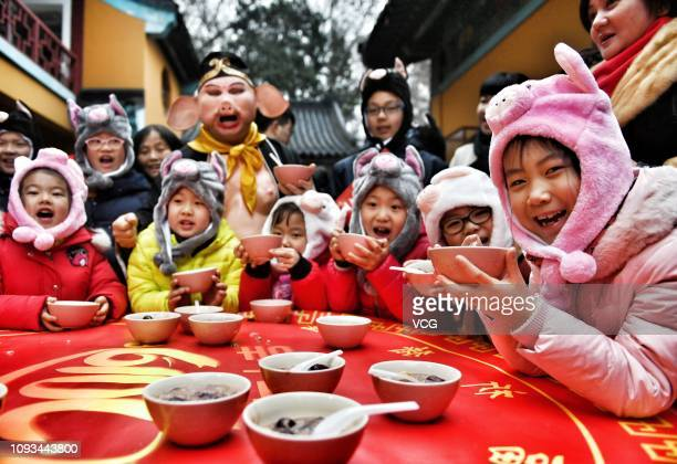 An actor dressed as Zhu Bajie one of the chief characters in 'Journey to the West' distributes Laba rice porridge to children at a temple during Laba...