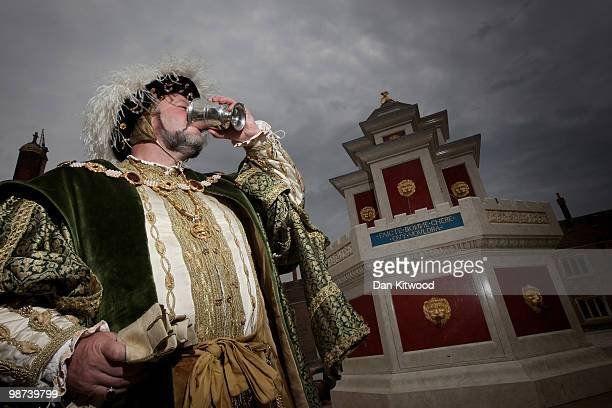 An actor dressed in historical costume poses during a photocall at the newly unveiled wine fountain in the inner courtyard at Hampton Court Palace on...