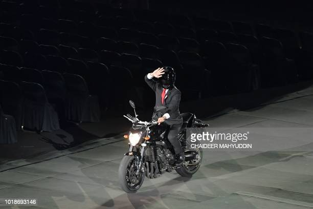 An actor impersonating Indonesian President Joko Widodo waves while riding a motorbike during the opening ceremony of the 2018 Asian Games at the...