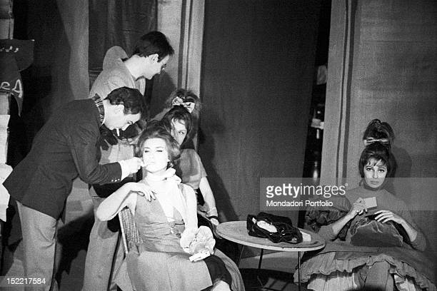 An actor lights on a cigarette to Ilaria Occhini interpreting Anna in the play 'Un marziano a Roma' the actress is sat at a table with other actors...