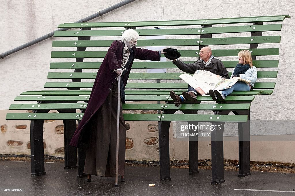 An actor on stilts walks past a giant park bench during a performance of the Theatre Somente as part of the Rhineland-Palatinate's culture summer's program on May 10, 2014 in Hachenburg, western Germany.