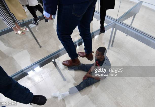 """An actor performs in """"Faust"""" by German artist Anne Imhof during the press preview of the 57th International Art Exhibition Biennale, on May 9, 2017..."""