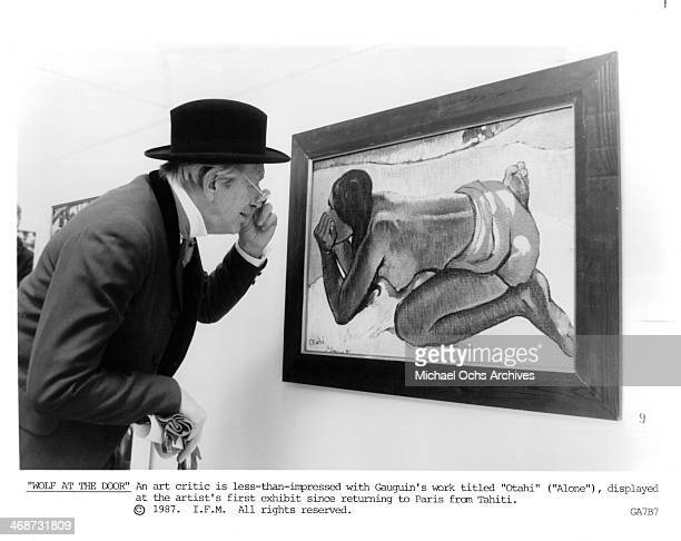 """An actor playing an art critic inspects the new work of Gauguin on set of the movie """"Oviri"""" , circa 1987."""