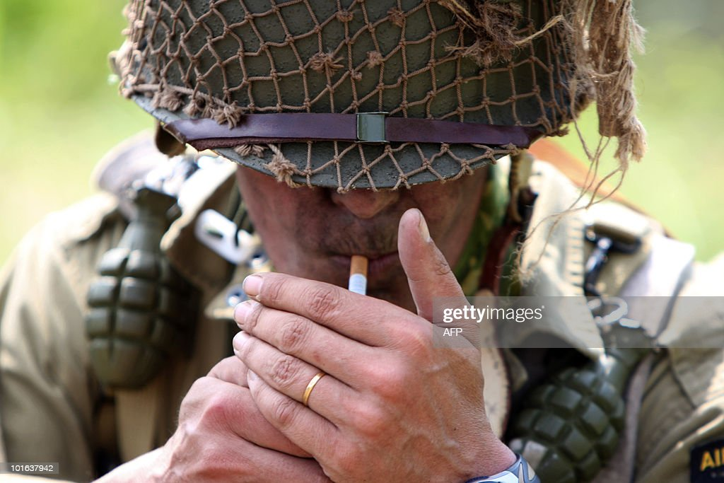 An actor, playing the role of an US soldier taking part in the 'Liberty March', smokes on June 5, 2010 in Carentan, western France, on the eve of the 66th anniversary of the D-Day Allied landings on the beaches of Normandy that marked the end of the WWII in June 1944. During the WWII, US troops faced German soldiers in violent fights at the so-called Hell's corner in La Barquette village.