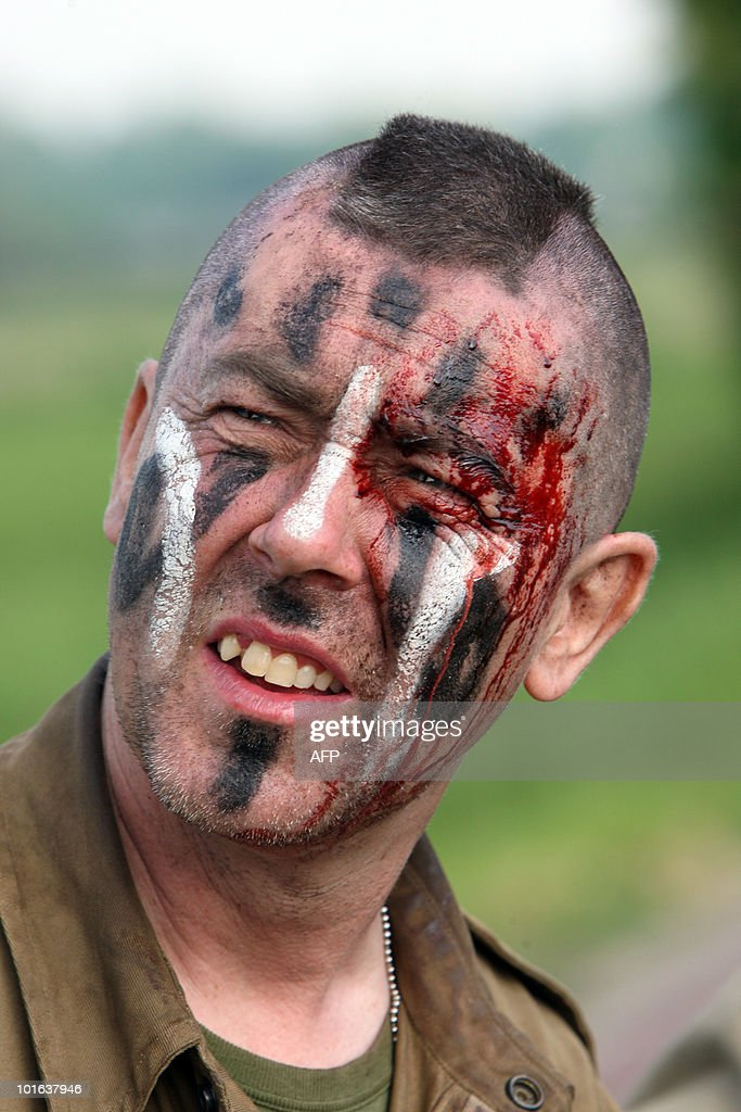An actor plays the role of an US soldier taking part in the 'Liberty March' on June 5, 2010 in Carentan, western France, on the eve of the 66th anniversary of the D-Day Allied landings on the beaches of Normandy that marked the end of the WWII in June 1944. During the WWII, US troops faced German soldiers in violent fights at the so-called Hell's corner in La Barquette village.