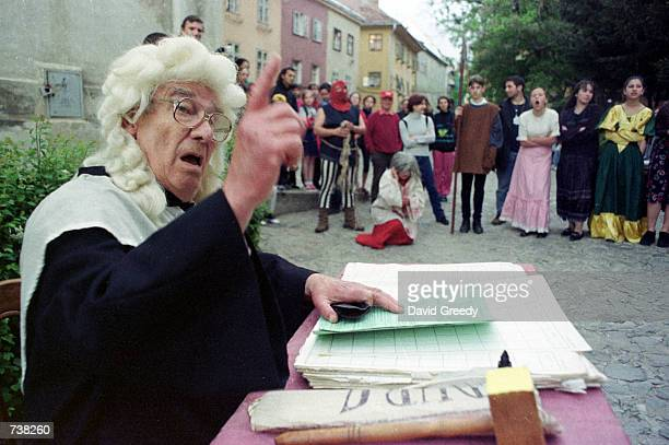 An actor portraying a judge presides over a mock medieval witch trial May 9 2001 inside the walled city of Sighisoara Romania The mock trial helped...