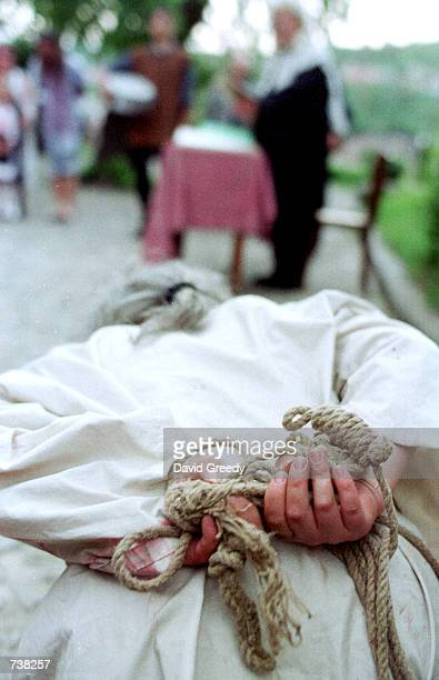 An actor portraying a witch is bound with rope for her mock medieval witch trial May 9, 2001 inside the walled city of Sighisoara, Romania. The mock...