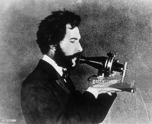 An actor portraying Alexander Graham Bell speaking into the Centennial telephone