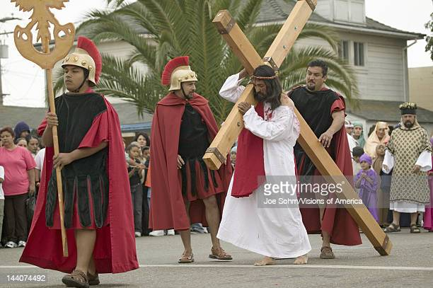 An actor portraying Jesus Christ carrying a cross past crowds on Good Friday Easter during the Passion play a dramatic reenactment of the trial...