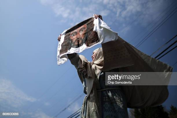 An actor portraying St Veronica holds up an image of Jesus during a traditional Via Crucis or Way of the Cross procession on the Christian Good...