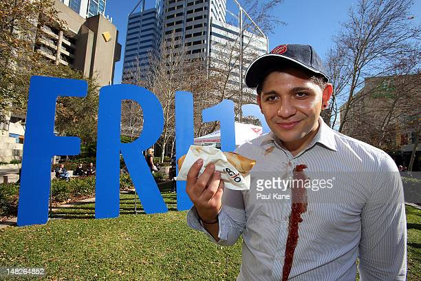 An actor poses after spilling sauce on his shirt at Central Park during a free BBQ to promote the 'Friday 13th Insurance' mock policy launch for...