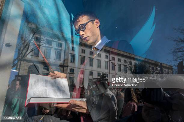 An actor posing as Harry Potter reads novels' texts sitting at the shopwindow in Lello Bookstore to during its 113th anniversary on January 13 2019...