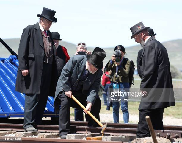 An actor taps the golden spike as he and others reenact the 150th anniversary of the driving of the Golden Spike on May 10 2019 in Promontory Utah...