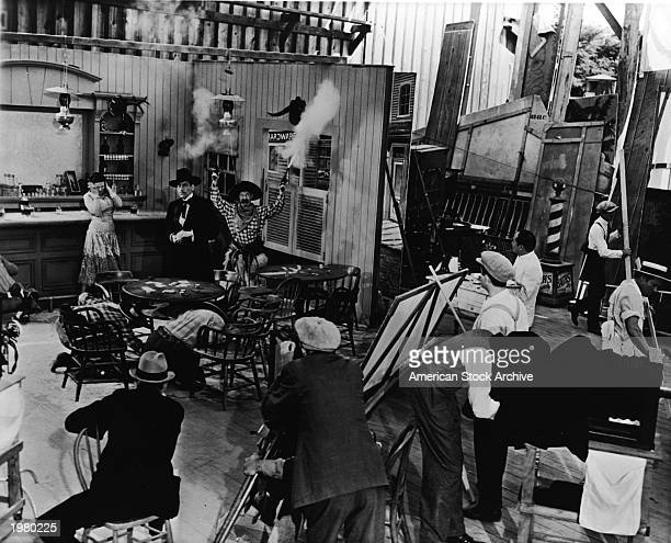An actor wearing a cowboy costume shoots two pistols in the air as other actors react on an Old West saloon studio set during the production of a...