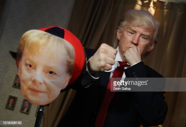 An actor wearing a silicon mask in the likeness of US President Donald Trump poses poses with a Hillary Clinton doll during a presentation at Madame...