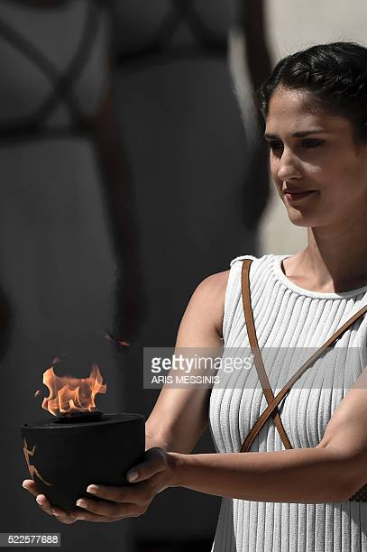An actress acting the pristess holds a cauldron with the Olympic flame at the Temple of Hera on April 20 2016 during a dress rehearsal of the...