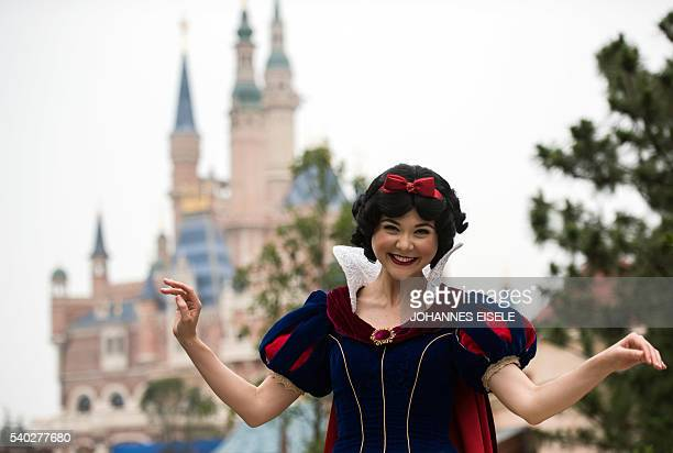 An actress dressed as 'Snow White' poses in front of the Enchanted Storybook Castle at Shanghai Disney Resort in Shanghai on June 15 2016 The Magic...
