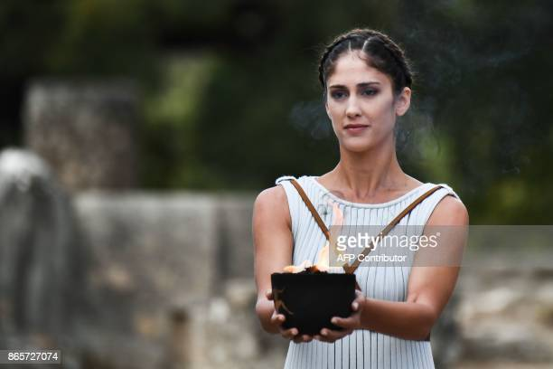 An actress holds the Olympic flame at the Temple of Hera in Olympia the sanctuary where the Olympic Games were born in 776 BC on October 24 2017...
