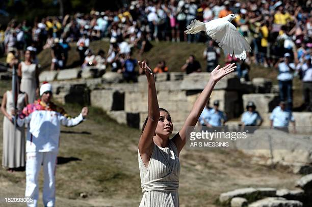 An actress in the role of a priestess releases a dove on September 28 2013 in ancient Olympia the sanctuary where the Olympic Games were born in 776...