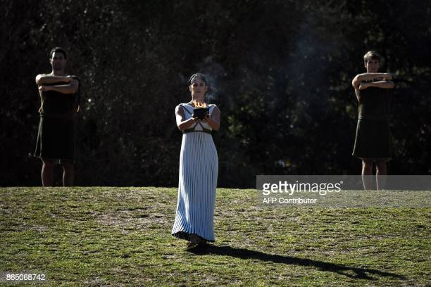 An actress performing as a priestess holds a pot with the Olympic flame at the Temple of Hera on October 22 2017 during a dressed rehearsal of the...