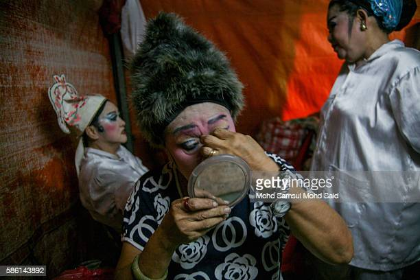 An actress puts on makeup at a makeshift theater before a performance during the Hungry Ghost Festival on August 5 2016 in Kuala Lumpur Malaysia The...